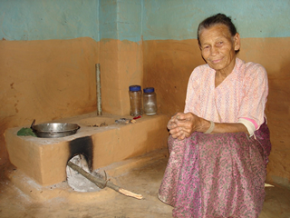Nepalesische Frau sitzt vor Lehmofen